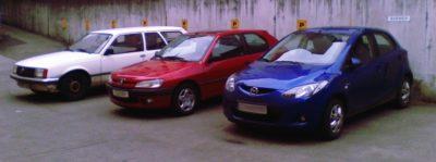 Weißer Opel Rekord E, roter Peugeot 306 und blauer Mazda 2